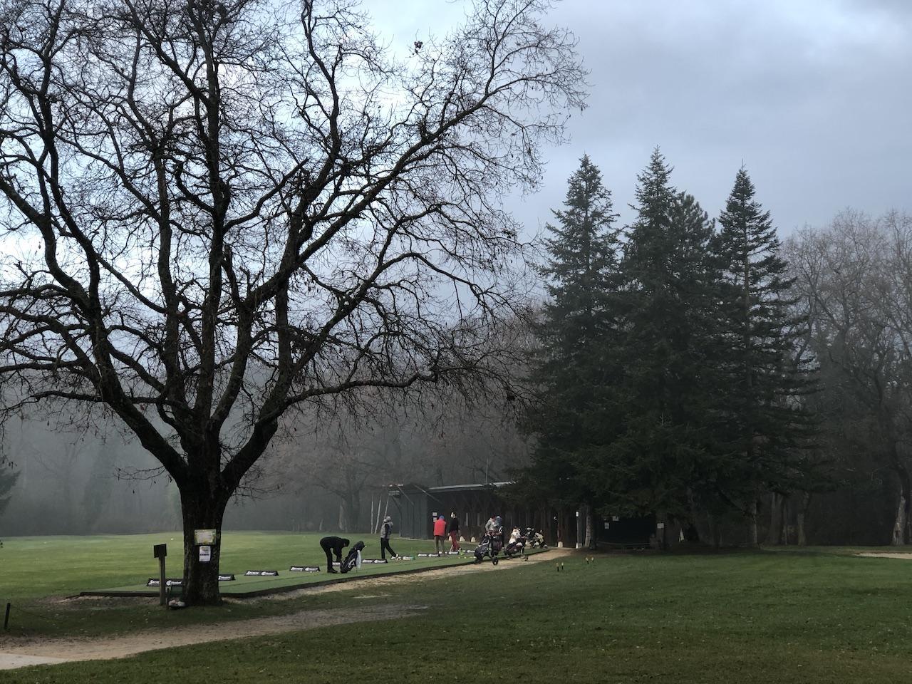 Quelques rares golfeurs au practice, tôt le matin